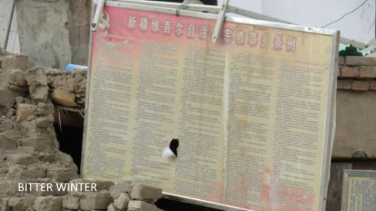 """Remnants of walls still display a bulletin board that says """"Xinjiang Uyghur Autonomous Region Regulations on Religious Affairs"""""""