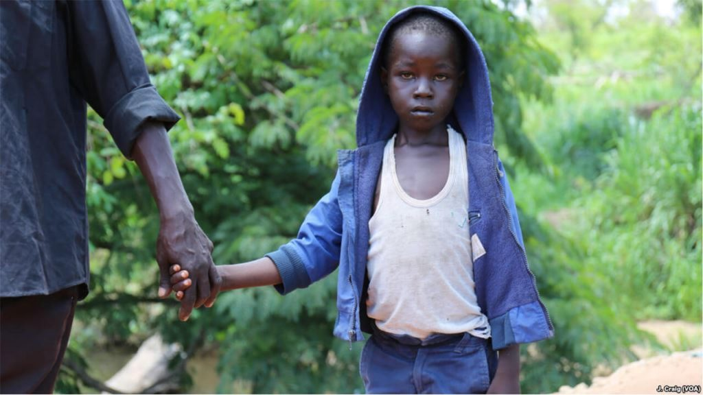 FILE - Seven-year-old John Wesley slowly crosses the border from South Sudan into Uganda with his father at the Busia border point, April 1, 2017, in Koboko, Uganda.