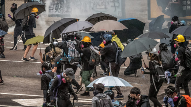 Hong Kong protestors and reporters need face masks and umbrellas to withstand tear gas attacks by the police