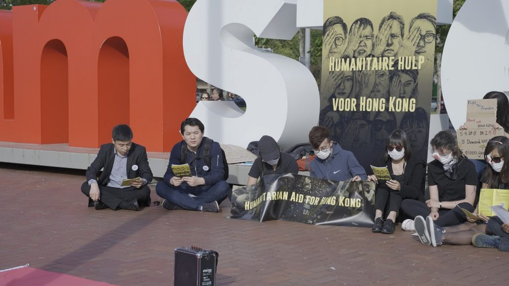 """Attendants sitting in the square and singing """"Glory to Hong Kong"""""""