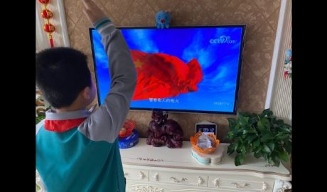 A primary school student gives a salute while watching a flag-raising ceremony on online class through TV at home in Shandong's Jiaozhou city.