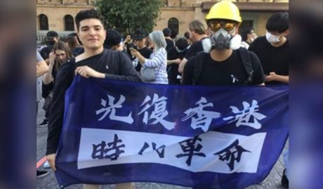 University of Queensland student Drew Pavlou (L) holds a banner supporting Hong Kong's pro-democracy movement