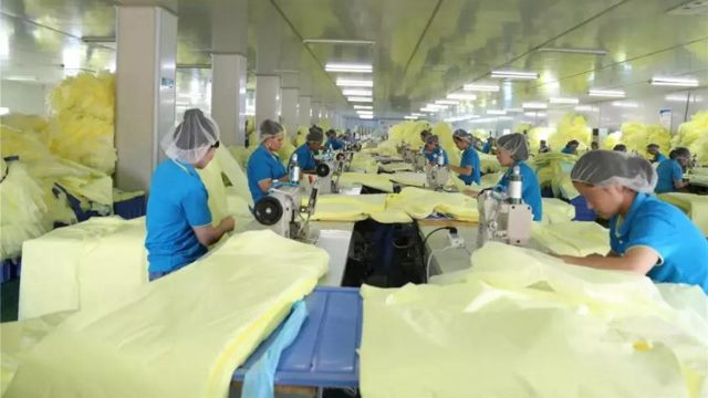 Uyghurs working in a factory's workshop in Hubei Province.