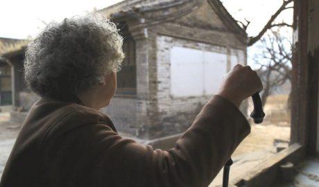An elderly woman awaiting her family