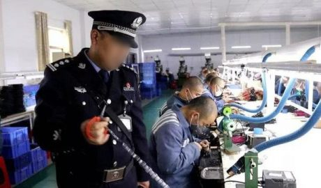 A guard supervises inmates working in a prison workshop