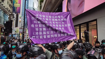 Riot police raises a warning flag on the national security law during a demonstration on July 1, 2020.