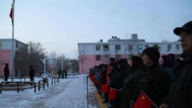 A residential community in Xinjiang organizes its residents for a flag-raising ceremony.