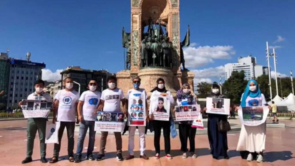 Uyghurs wearing T-shirts with images of missing relatives pose for a photo in front of the Republic Monument on Taksim Square in Istanbul, Aug. 17, 2020