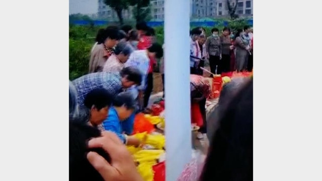 People burn incense and paper money in front of the Mao Zedong statue.