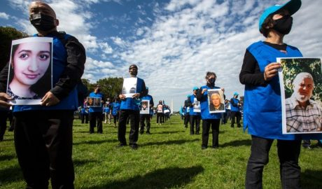 """Uyghur protesters hold up pictures of their family members during """"Resist CCP: Global Day of Action"""" in front of the Capitol Reflecting Pool in Washington D.C., Oct. 1, 2020."""