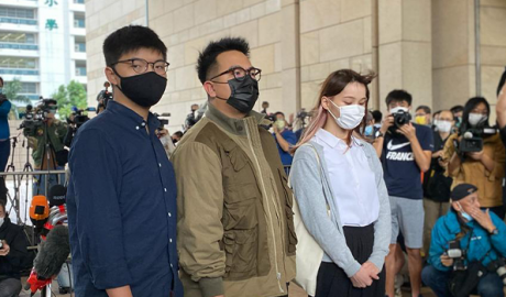 Hong Kong activists, from left, Joshua Wong, Ivan Lam and Agnes Chow arrive at a court in Hong Kong,