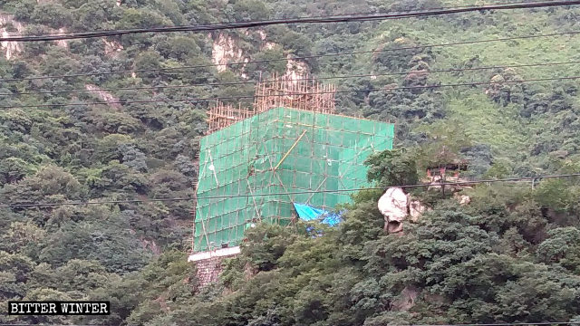 The scaffolding around the three-faced Guanyin statue was built ahead of its removal.