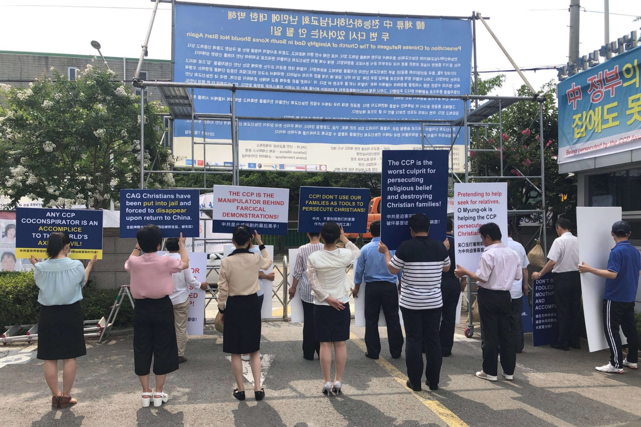 CAG Christians holding sign boards at the entrance of the Onsu CAG premises, protesting against the CCP for using their family members to stage false demonstrations